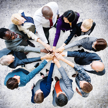 Group of coworkers in a circle stacking their hands together.
