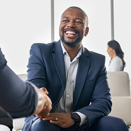 Black businessman smiling while shaking someone's hand
