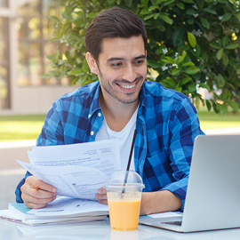 Young guy holding papers looking at his laptop
