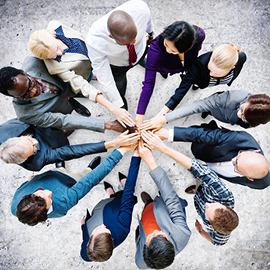 Group of people in a huddle with their hands meeting in the center
