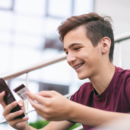 Boy is smiling while holding his debit card and cell phone.