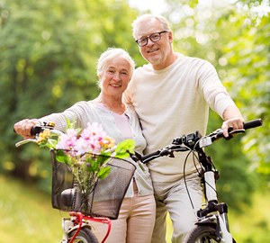 Older couple out in nature smiling while riding their bikes.