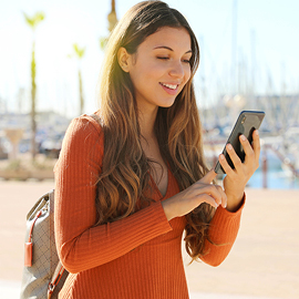 Young woman smiling while looking at her cell phone