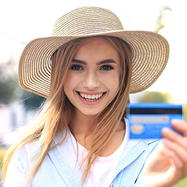 Young woman wearing a straw hat smiling while holding a credit card