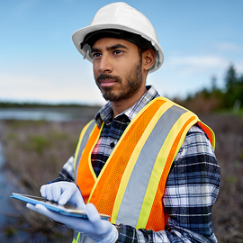 Water worker wearing a flannel shirt, hard hat and vest on a job site