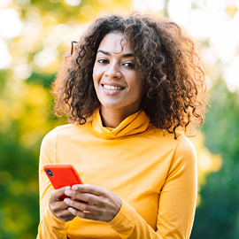 Female smiling holding a cell phone