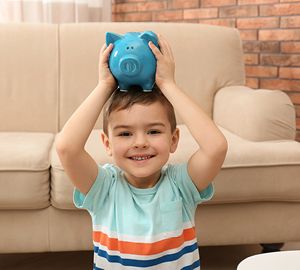 Young boy smiling while holding a blue piggy bank on his head.
