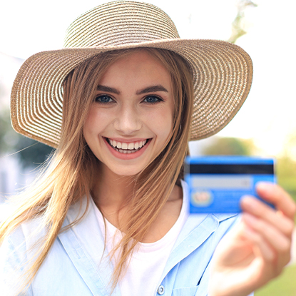 Young girl wearing a straw hat smiling while holding her debit card.