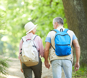 Older couple with back packs on walking on a trail.
