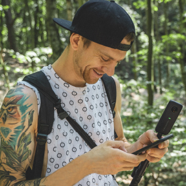 Young man in a forest looking at his cell phone