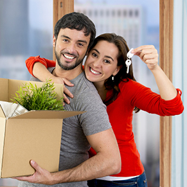 Young couple holding packing boxes and keys to their new home