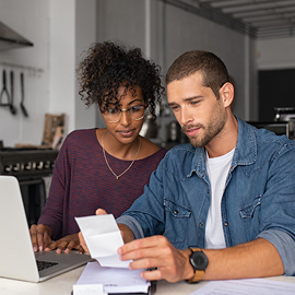 Interracial couple working on a laptop and looking at paperwork