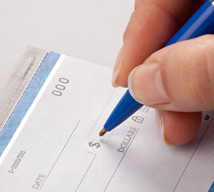 Person writing a check with a blue pen in his hand.