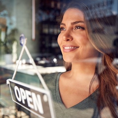 Businesswoman smiling through the window of her shop. An open sign is on the door.