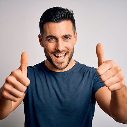 Man is smiling while doing a thumbs up.