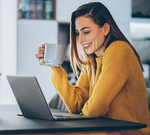 Young woman holding a cup of coffee smiling while working on her laptop.