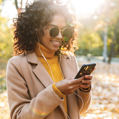 Black woman wearing sunglasses and smiling while holding her cell phone outdoors.