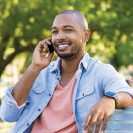 Young black man sitting on a park bench, smiling while talking on his cell phone