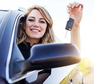 Young woman sitting in her car smiling while holding keys to her new car in her hand,