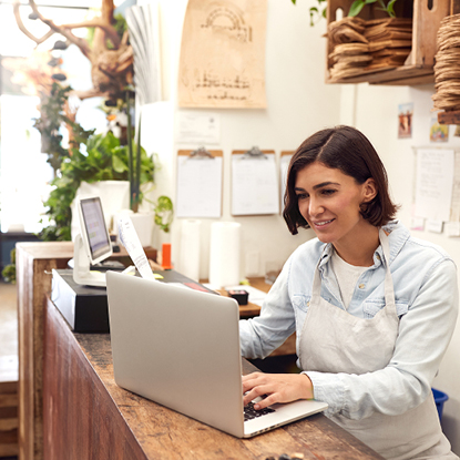 Shop worker wearing a white apron and smiling while using a laptop at her business.