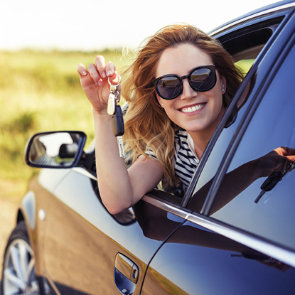 Young woman sitting in her car smiling while holding keys to her new car.