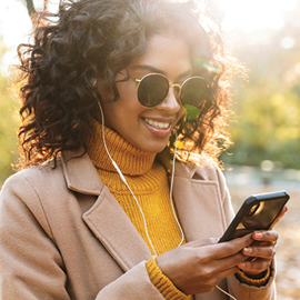 Woman wearing round sunglasses with ear buds in looking at her cell phone