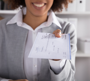 Young black woman holding a cashiers check.