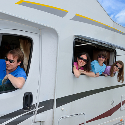 Family smiling while hanging out the windows of their RV.